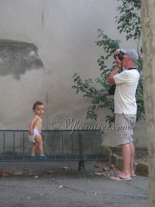 Mr Lifecruiser as a photographer is watched by kid, Medieval village, Southern France, Copyright Lifecruiser.com